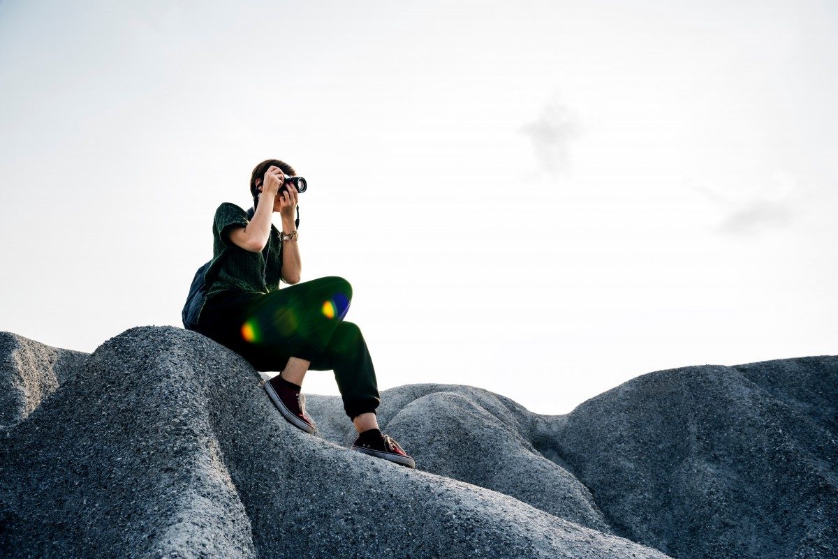 Photographer Sitting on Rock in Nature Photographing Landscape