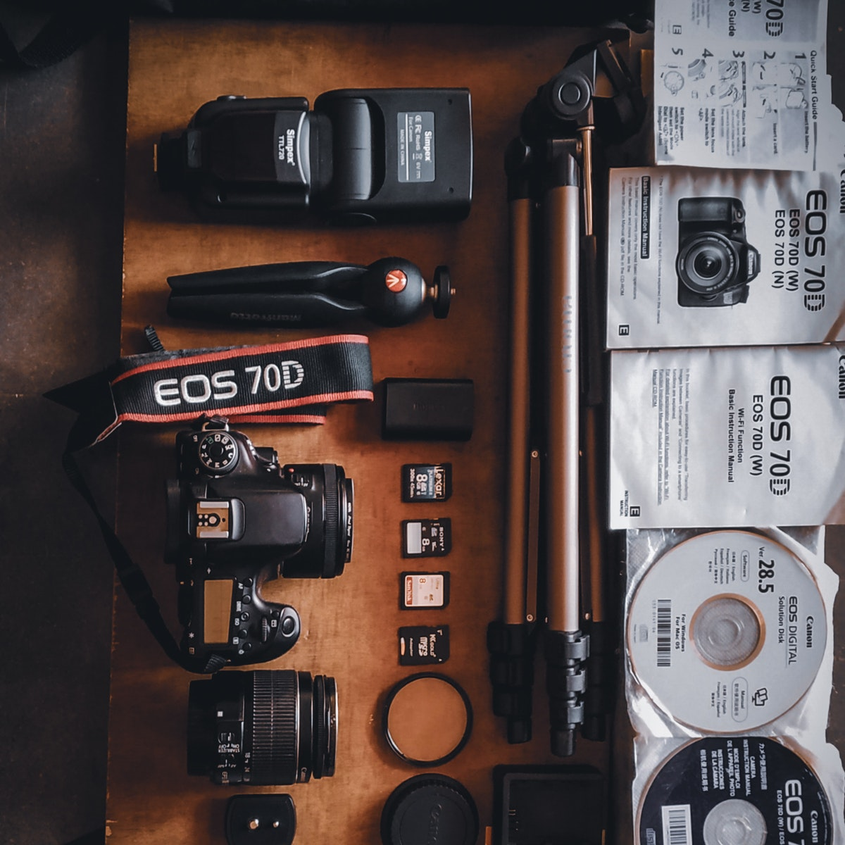 Camera Layout with Different Camera Equipment Like SD Cards, CDs, Lenses and a Tripod