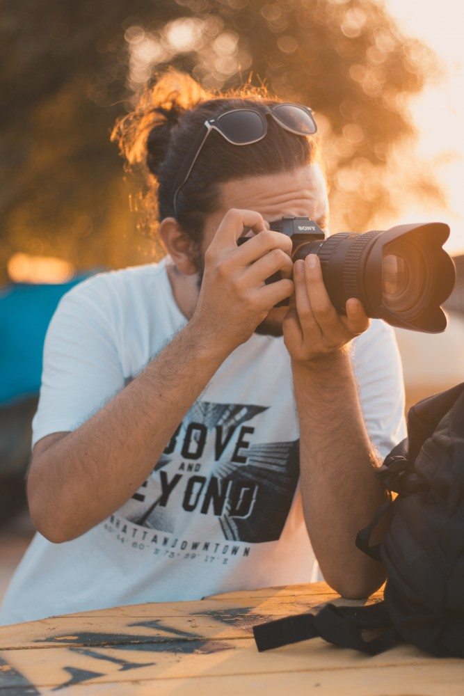 Male Photographer With Long Hair and Sunglass Taking Photos of Scenery Around Him with His Camera