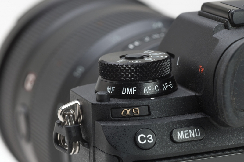 The lower ring of the combined drive and focus stack is used to select the focus mode, here set to continuous autofocus. The upper portion of the dial selects the frame rate.
