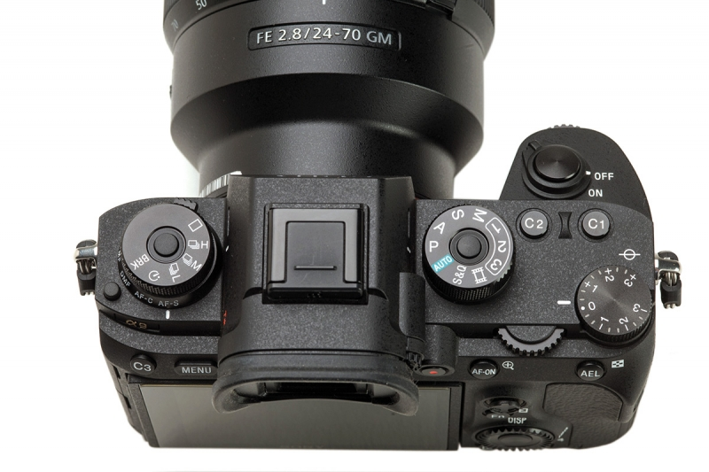 The three dials on the top of the body are combined drive and focus mode stack to the far left, a mode selection dial near the viewfinder, and an exposure compensation dial to the far right.