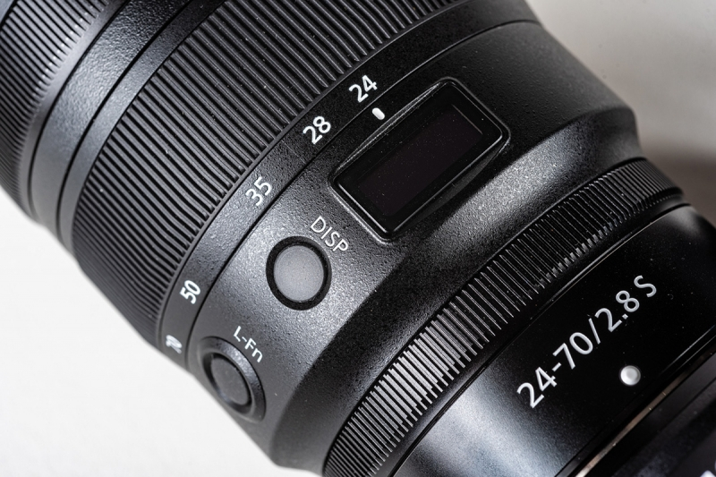 The DISP (display) button controls what you see through the window on the lens.